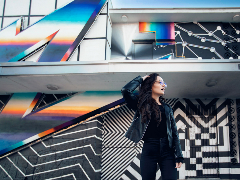 woman of generation z posing in front of a mural