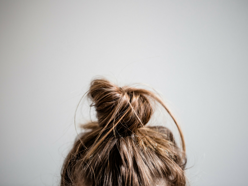 shot of a womans' top knot in need of bookedin