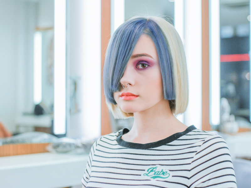 girl with blue and blonde hair sitting in a salon