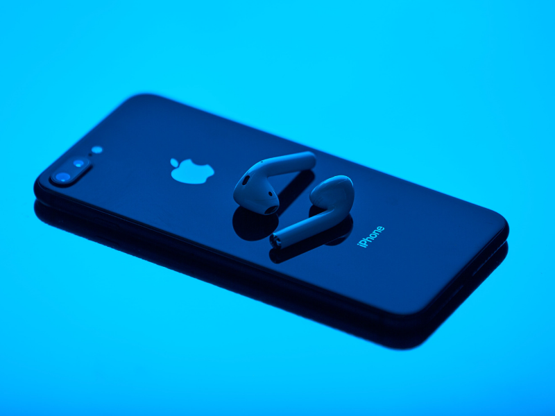 apple iphone with earbuds on a bright blue background