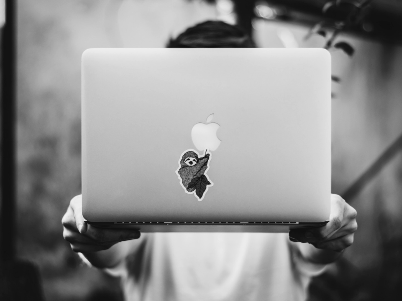 a man holding an apple laptop with outstretched arms