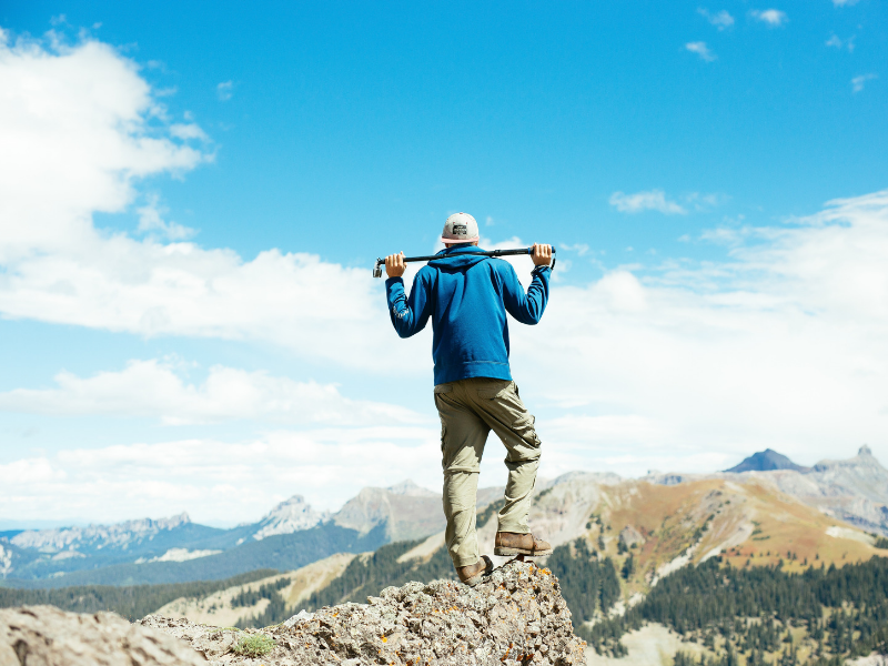 young man on top of a mountain with blue sky