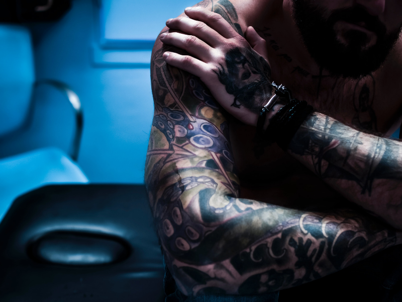 close up shot of a tattooed man sitting in his shop