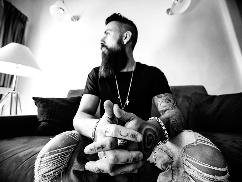 close up shot of a tattooed man on a couch