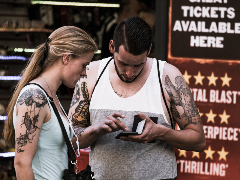 two people staring at their cell phone in front of a theatre