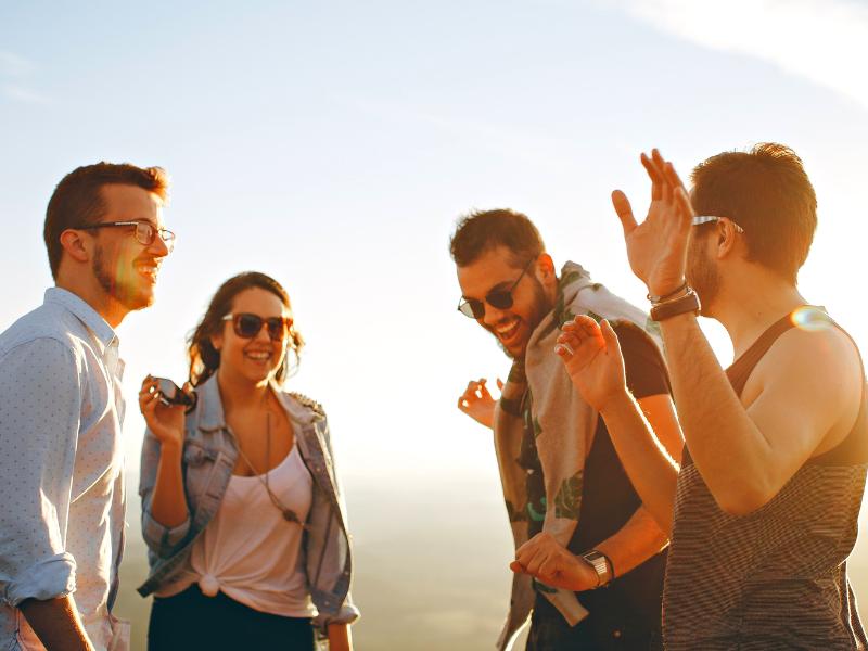 4 young millennials celebrate at sunset
