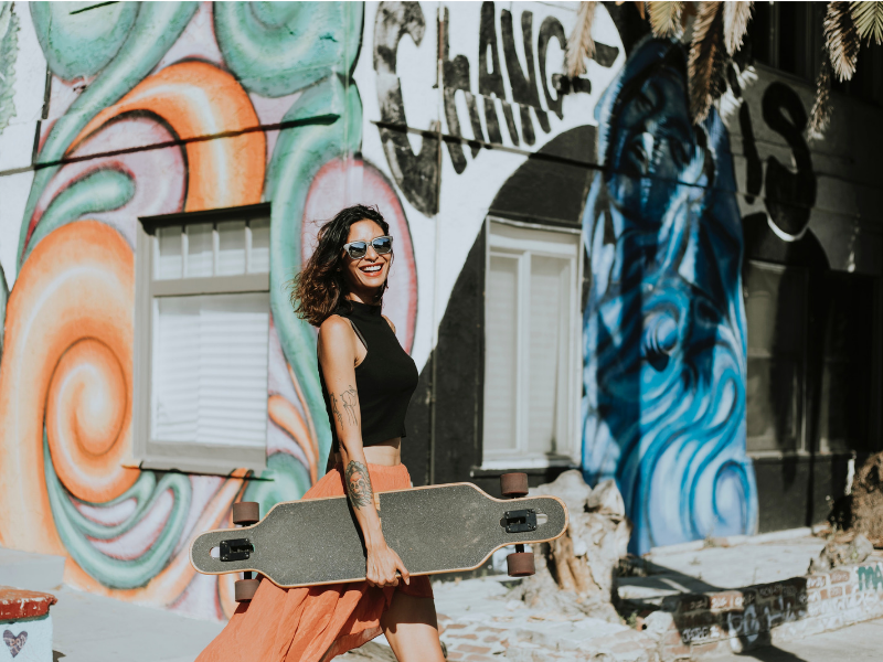 woman with tattoos is holding a longboard