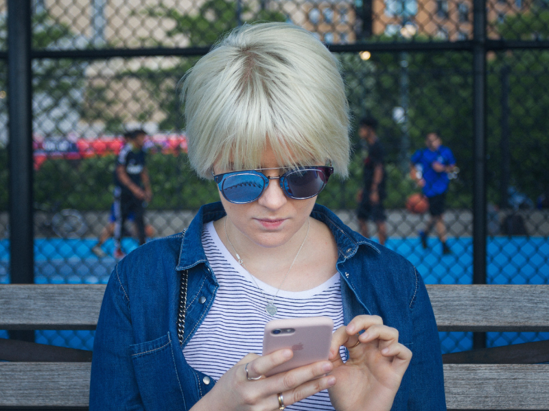 young blond woman is holding her phone