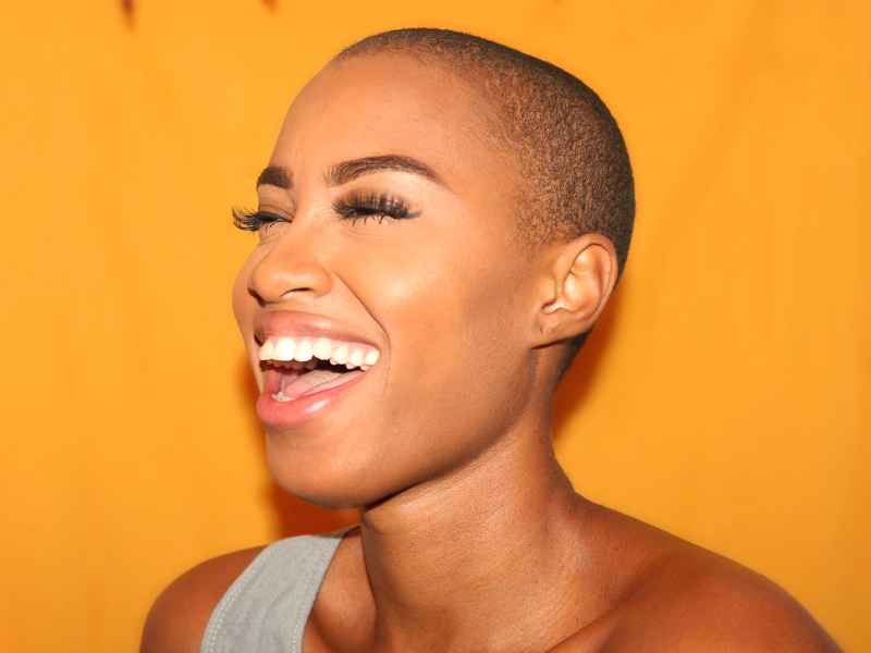 young woman with shaved head laughs in front of a bright yellow background