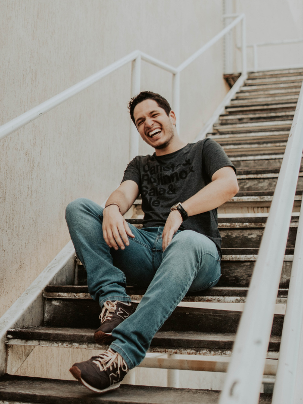 a laughing man on the stairs wearing a t-shirt and jeans