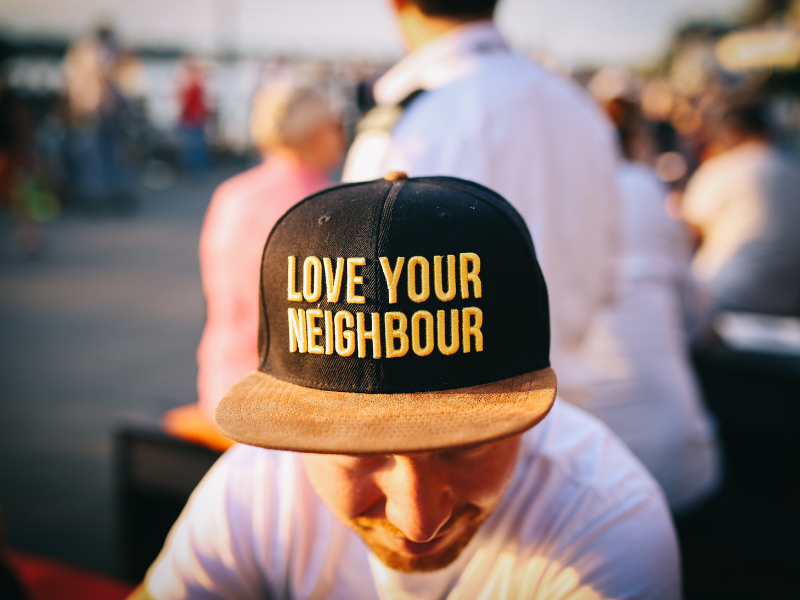 close up of a man wearing love your neighbor hat