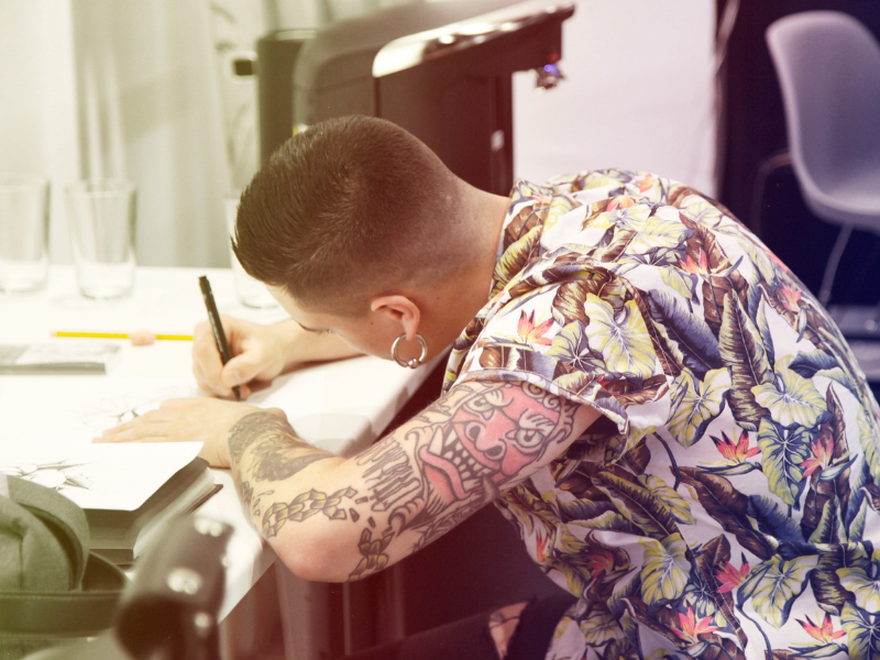 a tattoo artist is sketching a tattoo in his shop