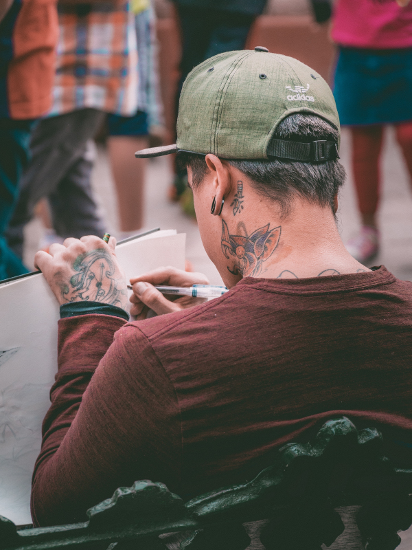 man with tattoo on his neck is writing in a notebook