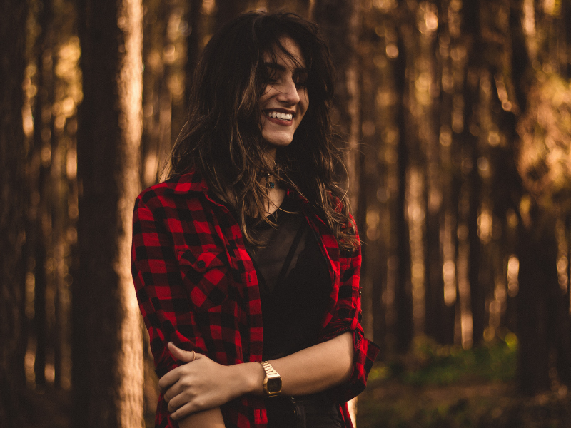 woman smiling in the woods wearing a flannel shirt
