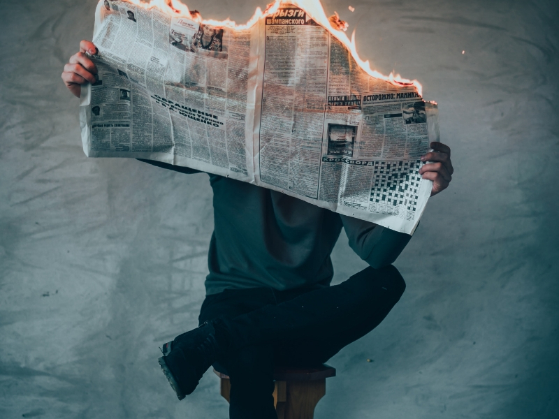 man sitting in a chair holds a burning newspaper