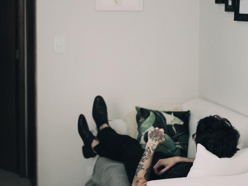 man lying on couch unproductive