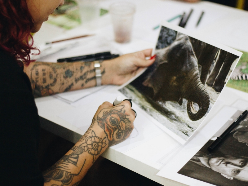 a woman with tattoos is sketching from a photograph