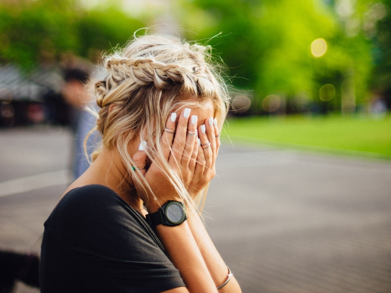 blond woman covers her face after making a mistake