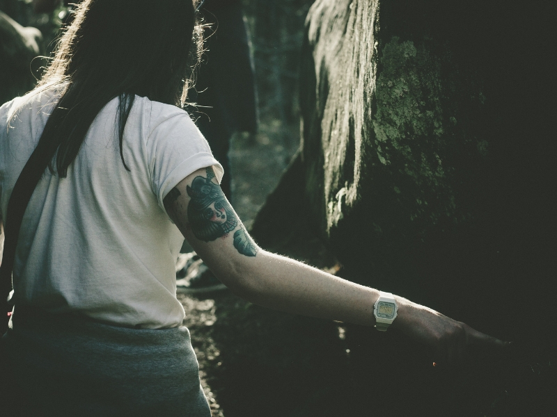 a woman with cap sleeve tattoo stands in the woods
