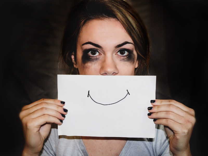 sad woman holds paper smile to face