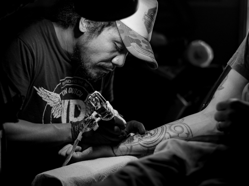 man in a tattoo shop doing a tattoo