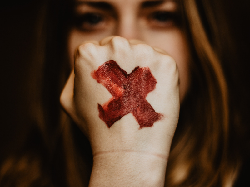 "close up of a woman's fist with a red ""x"" on it"