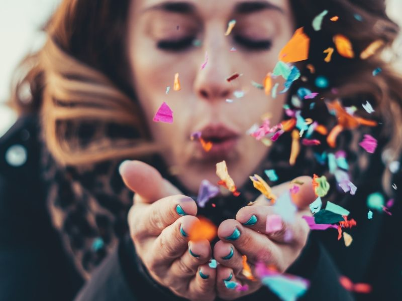 a woman is blowing confetti which is a great client visit decoration ideas