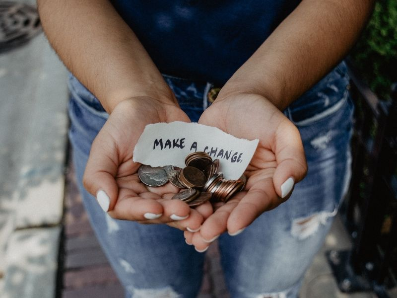 close up of two hands holding change and a sign saying _make a change