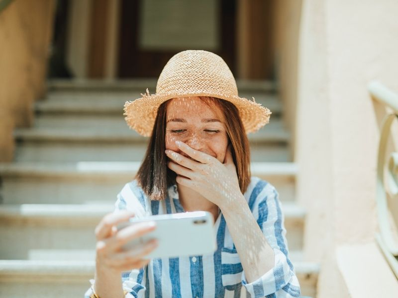 woman is looking at her phone and hiding her amused expression