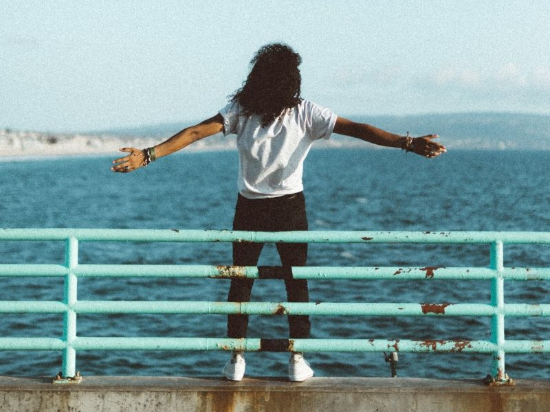 young woman standing by the ocean spreading her arms