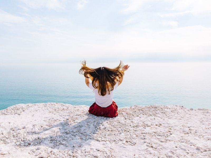woman sitting on th edge of a cliff in the wind