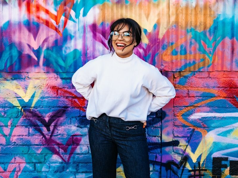 a young woman laughing in front of a graffiti covered wall