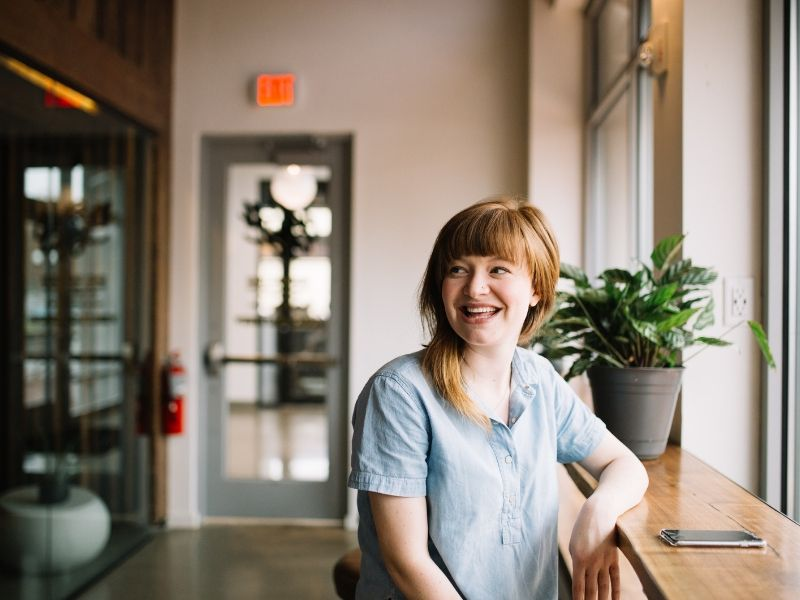 a happy young woman ready to set boundaries in a coffee shop