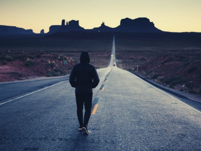 man walks down the middle of an empty highway