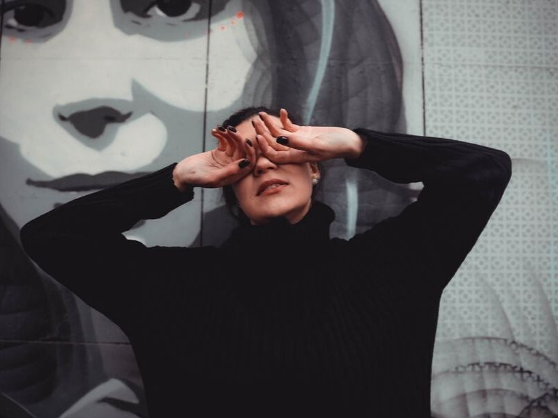woman covers her eyes in front of a wall