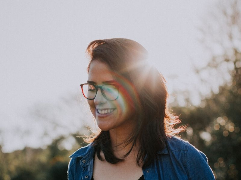 woman smiling with the sun in the background