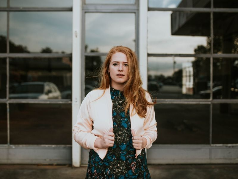 red headed woman in front of a building post COVID-19