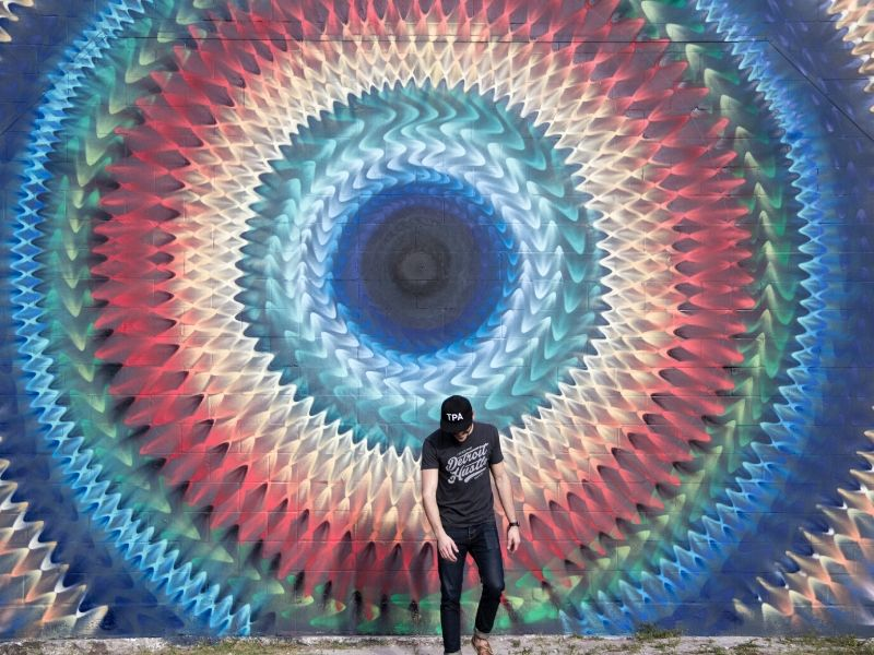 man in front of a standout mural