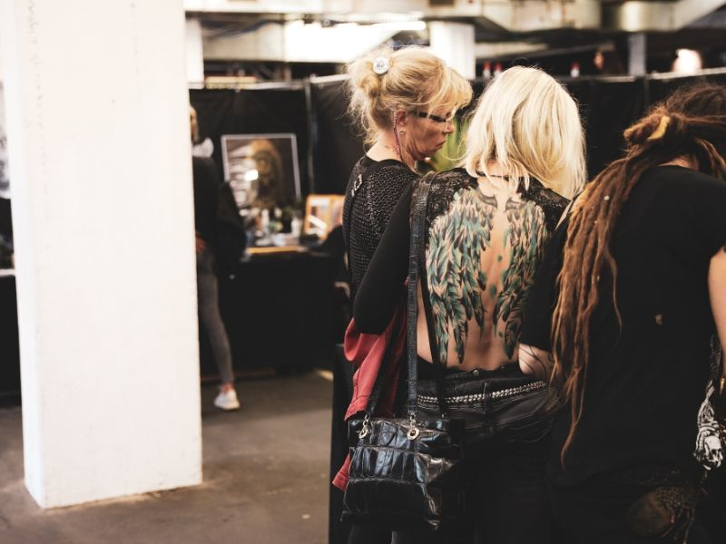 three tattoo artists looking for new clientsat a convention